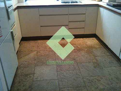 unsleaed_clean_slate_tiles_in_kitchen_floor_with_white_cupboards